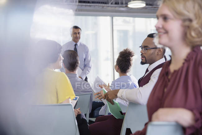 Business people talking in conference audience — Stock Photo