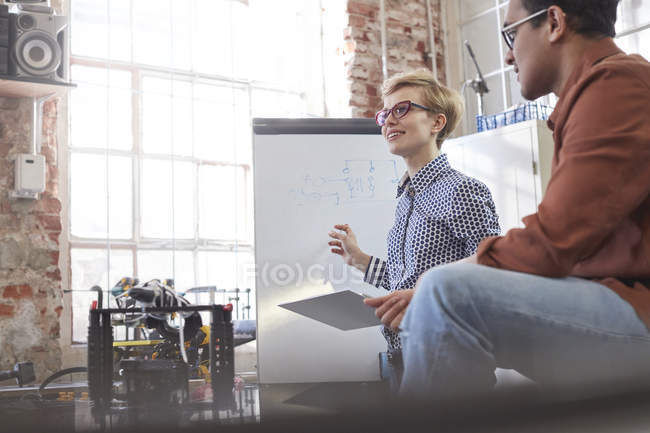 Smiling female designer with clipboard brainstorming at flipchart — Stock Photo