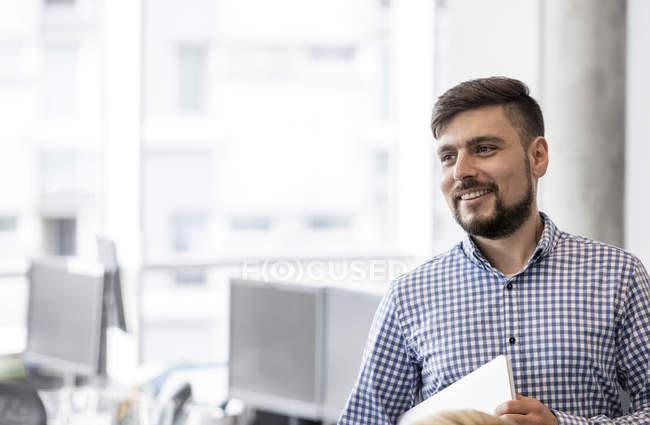 Lächelnder Geschäftsmann schaut im Amt weg — Stockfoto