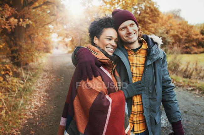 Lächelndes, liebevolles Paar umarmt sich im Herbstpark — Stockfoto