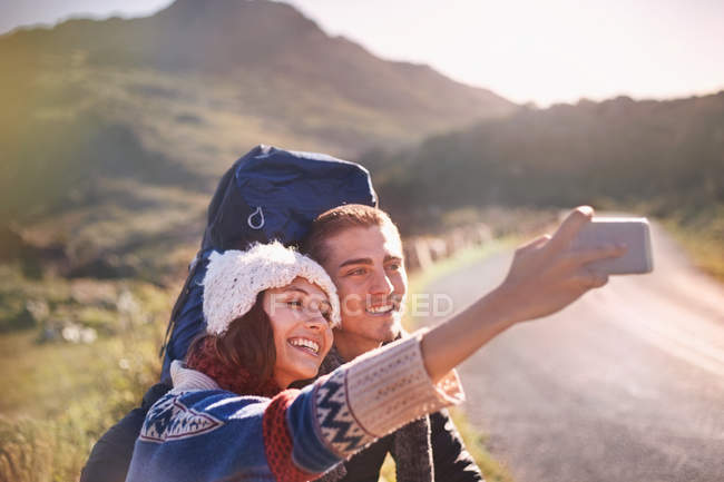 Young couple with backpacks hiking taking selfie with camera phone on sunny, remote road — стокове фото
