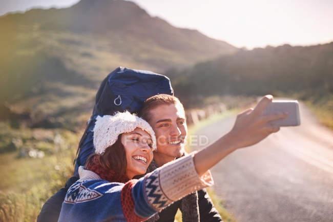 Pareja de jóvenes con mochilas senderismo selfie de toma con la cámara del teléfono en camino soleado, remoto - foto de stock