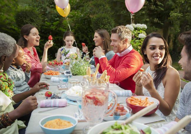 Сім'я і друзі, насолоджуючись саду дні народження в патіо таблиці — стокове фото