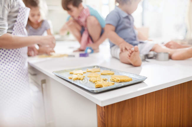 Mother and children baking cookies in kitchen — Stock Photo