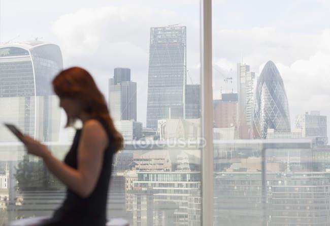 Бизнесвумен, использующая цифровой планшет у городского окна с видом на город, Лондон, Великобритания — стоковое фото