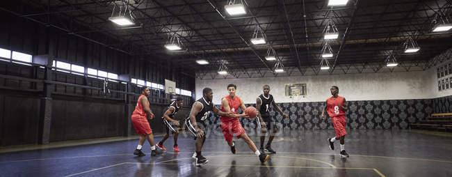Молоді чоловіки баскетболістів відіграють гри на суді в гімназії — стокове фото