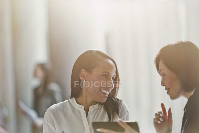 Smiling businesswomen talking, using digital tablet — Stock Photo