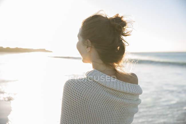 Jeune femme enveloppée dans une couverture sur la plage — Photo de stock