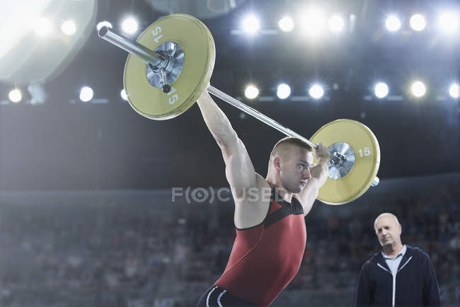 Trainer beobachten männliche Gewichtheber hockenden Langhantel overhead in arena — Stockfoto