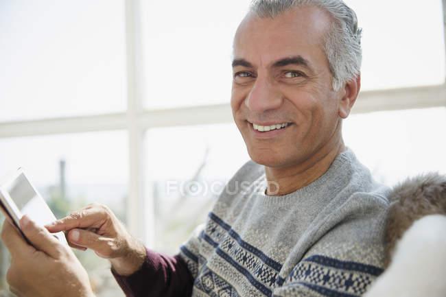 Portrait smiling senior man using digital tablet — Stock Photo