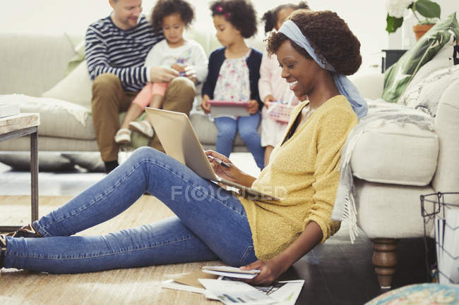 Smiling mother with laptop paying bills online with family in background — Stock Photo