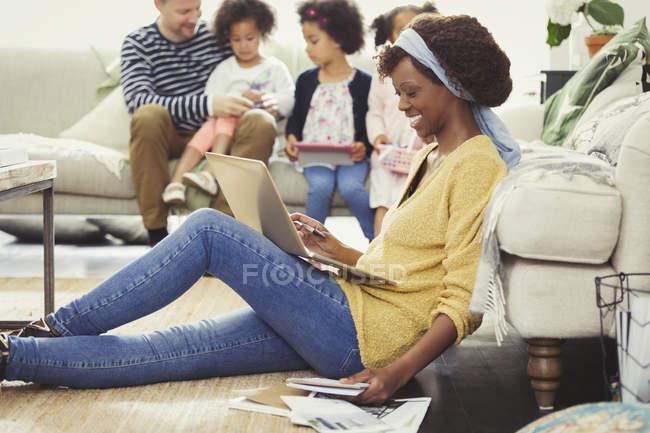 Lächelnde Mutter mit Laptop bezahlen Rechnungen online mit Familie im Hintergrund — Stockfoto