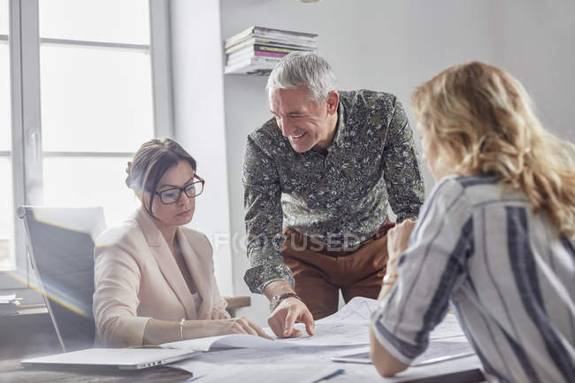 Architects discussing and reviewing blueprints in conference room meeting — Stock Photo