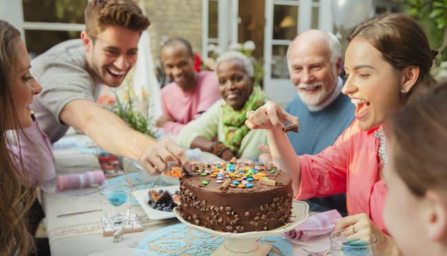 Famille atteignant pour candy sur gâteau d'anniversaire au chocolat à la table de patio — Photo de stock