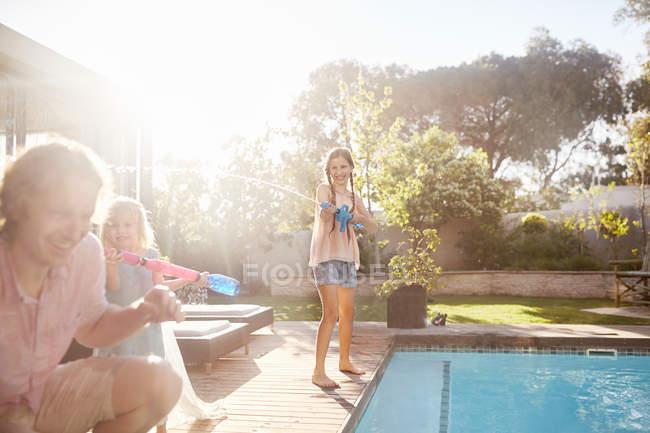 Дочка з навігація бандита пістолет обприскування батька з водою у Сонячний літній біля басейну — стокове фото