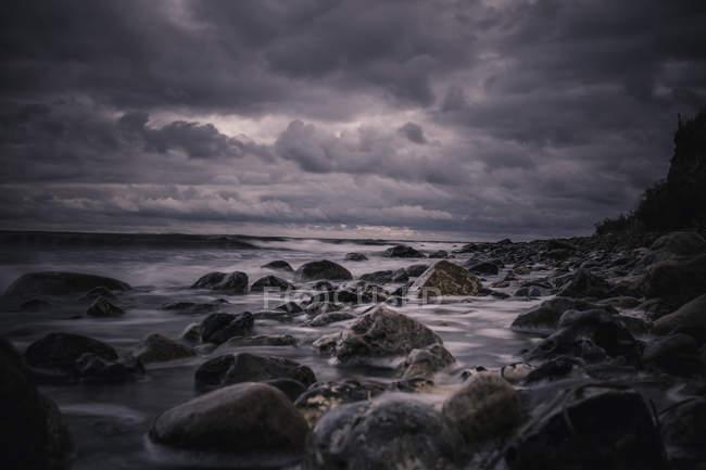Large rocks on stormy, overcast nighttime beach, Bisserup, Denmark — Stock Photo