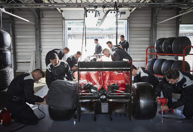 Pit crew working on formula one race car in repair garage — Stock Photo