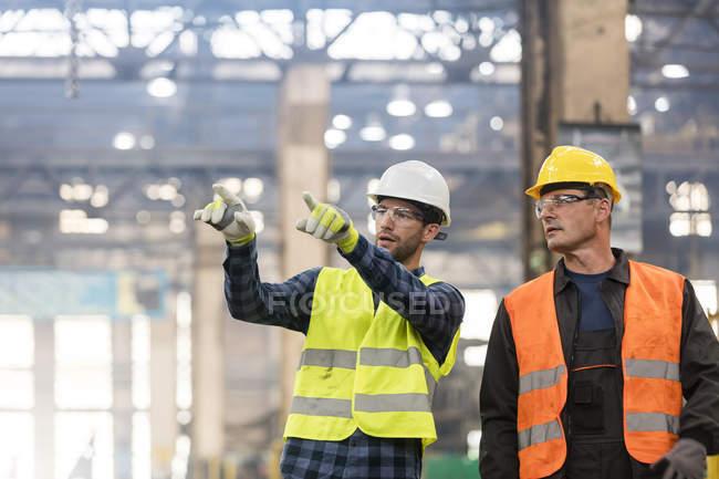 Сталеві працівників говорити і вказуючи на заводі — стокове фото