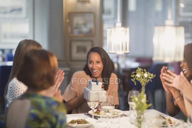 Freunde klatschen für Frau, die Geburtstag mit Geschenk am Restauranttisch feiert — Stockfoto