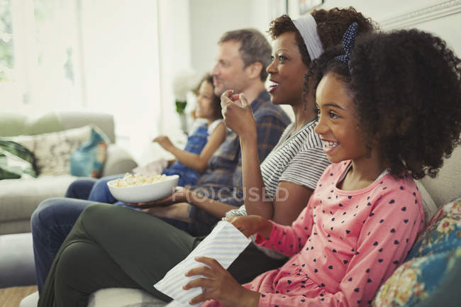 Young multi-ethnic family watching movie and eating popcorn on sofa — Stock Photo