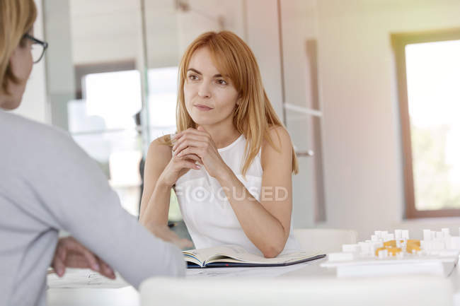 Attentive businesswoman listening to colleague in meeting — Stock Photo