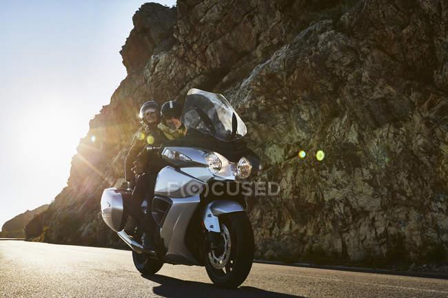 Пара їзда мотоцикл Сонячний дорога вздовж скелястій Скеля — стокове фото