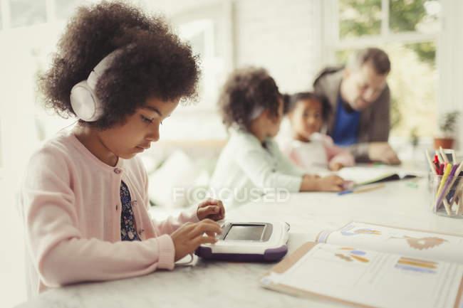 Mädchen mit Kopfhörern mit digitalem Tablet bei den Hausaufgaben am Tisch — Stockfoto