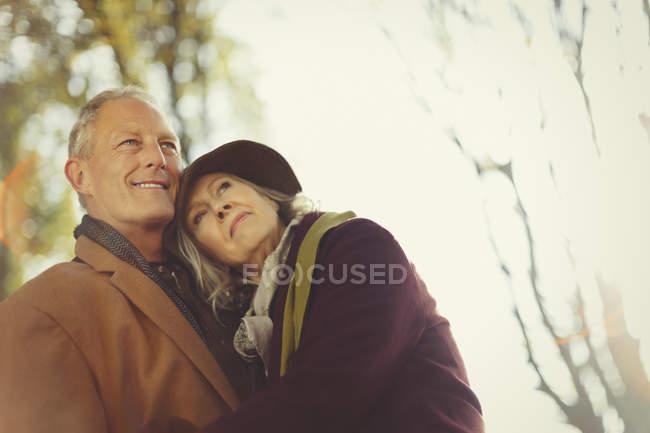 Affectionate, serene senior couple in autumn park — Stock Photo