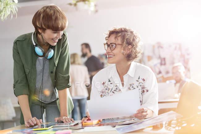 Professionisti del design femminile sorridenti che rivedono le prove in ufficio — Foto stock