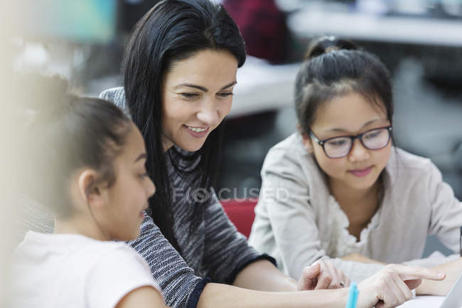 Female teacher and girl students using laptop in classroom — Stock Photo