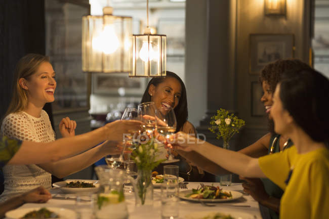 Lächelnde Freundinnen stoßen Weißweingläser am Restauranttisch an — Stockfoto