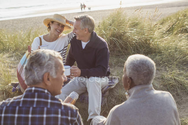Senior couples drinking coffee and relaxing on beach — Stock Photo