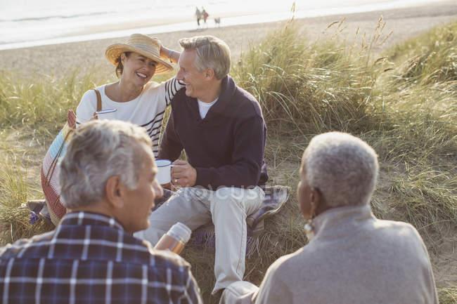 Senioren trinken Kaffee und entspannen sich am Strand — Stockfoto