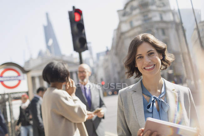 Portrait smiling, confident businesswoman on sunny urban city street — Stock Photo