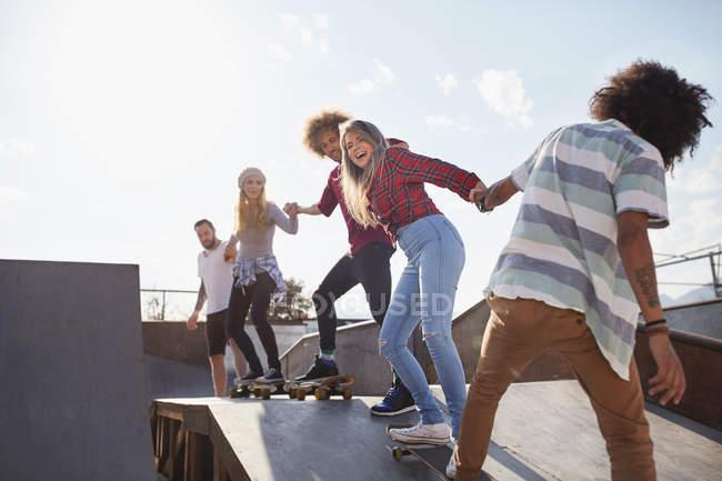 Друзів на скейтборд, тримаючись за руки поспіль на рампу в Сонячний Скейт-парк — стокове фото