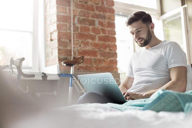 Человек с ноутбуком на кровати в квартире — стоковое фото