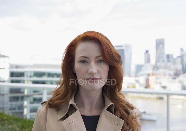 Portrait serious, confident businesswoman with red hair on urban balcony with city view — Stock Photo