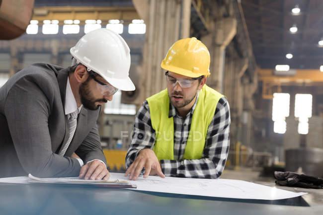 Менеджер і інженер рецензування креслення в сталевих заводу — стокове фото