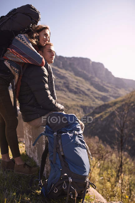 Young couple with backpacks looking at sunny view — Stock Photo