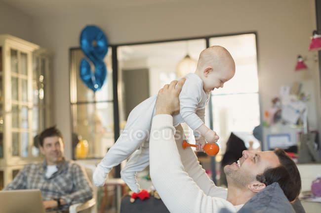 Мужчины гей родителей, играя с маленьким сыном в гостиной — стоковое фото