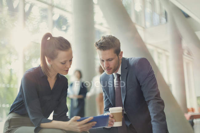 Business people drinking coffee and using digital tablet in office lobby — Stock Photo