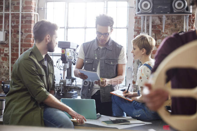 Designers meeting, using clipboard and laptop in workshop — Stock Photo