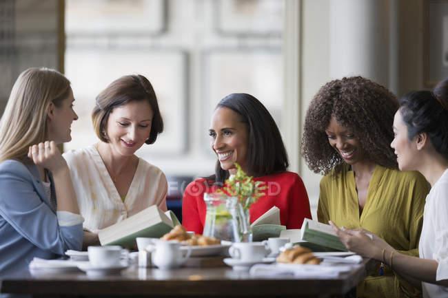 Женщины-друзья обсуждают книгу книжного клуба за столом ресторана — стоковое фото