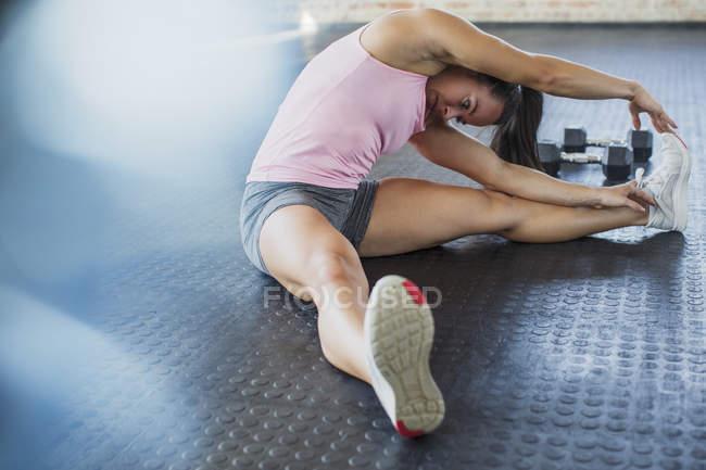 Jeune femme étirant jambe et côté dans la salle de gym — Photo de stock