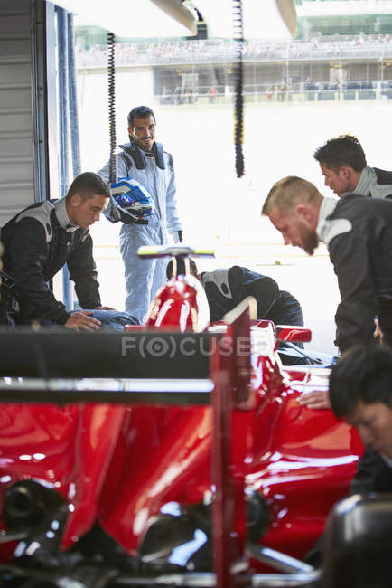 Formula one driver watching pit crew working on race car in repair garage — Stock Photo