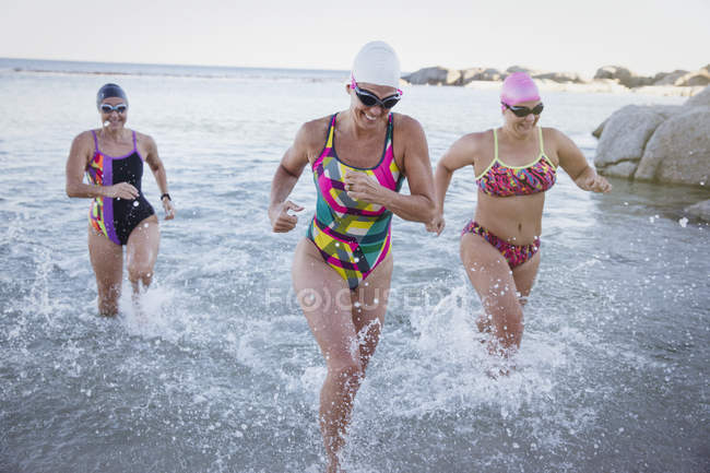 Female active swimmers running at ocean outdoors — Stock Photo