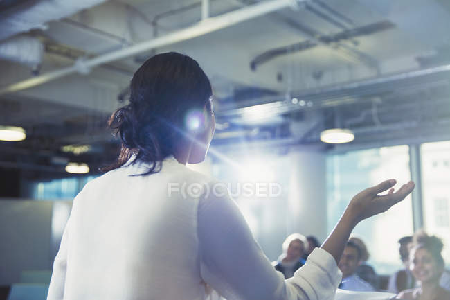 Businesswoman gesturing, leading conference presentation — Stock Photo