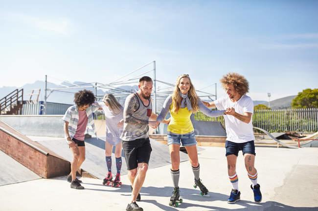 Друзів на роликових ковзанах на Сонячний Скейт-парк — стокове фото