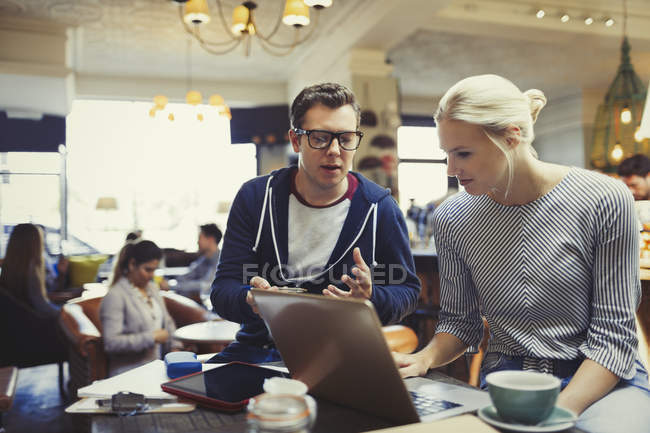Creative business people using laptop in cafe — Stock Photo