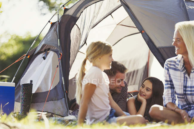 Smiling family talking and relaxing outside sunny tent — Stock Photo